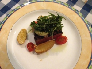 A grilled 8 oz. Angus Beef Filet, served with Fingerling Potatoes Confit in Frantoia Olive oil, fresh rosemary, and arugula tossed in balsalmic vinegar.