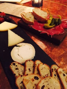 An assortment of three cheeses, some jamon, and bread.